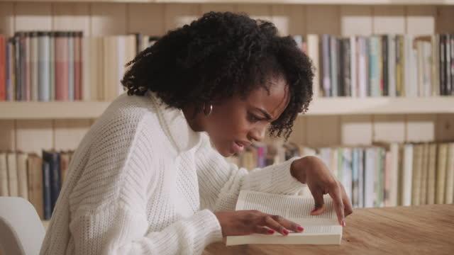 vidéos et rushes de femme africain d'ethnicité affichant le livre fascinant dans le salon. réaction émotionnelle pour la torsion d'intrigue. - écrivain