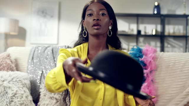 african ethnicity woman throwing a bowler hat. girls night fun - hat stock videos & royalty-free footage