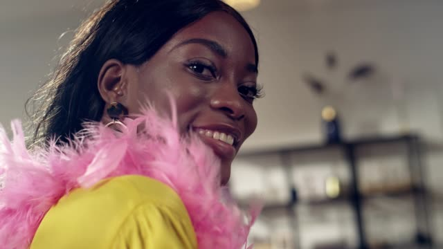 african ethnicity woman trying on feather boa. seduction - seduction stock videos & royalty-free footage