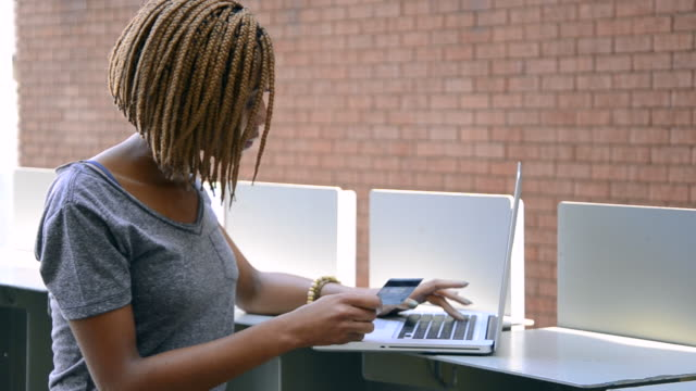 MS of African Ethnicity woman using laptop for online shopping / Johannesburg, Gauteng, South Africa