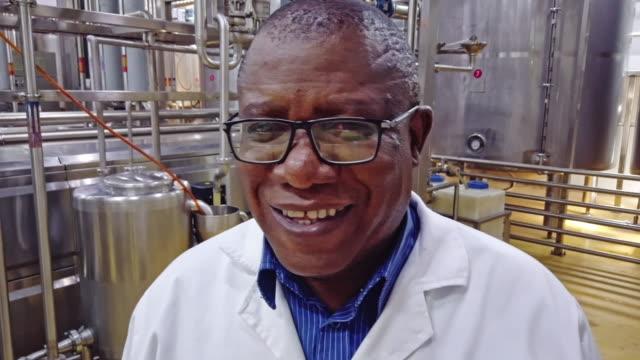 vídeos de stock, filmes e b-roll de gerente africano da fábrica que sorri na câmera - wisdom