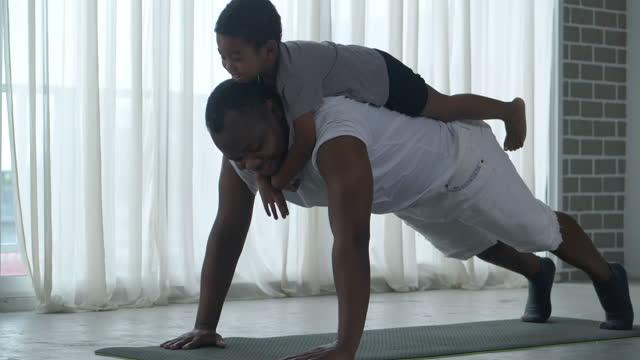 vidéos et rushes de famille africaine de père étirant des muscles, séjour d'entraînement à la maison tandis que son petit fils âgé de 3 ans sur son dos ensemble pendant la distanciation sociale ensemble restent à la maison pour empêcher des épidémies. exercices a - new age concept