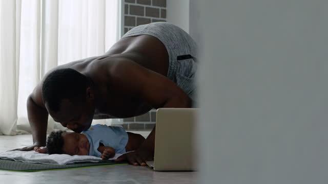 vidéos et rushes de famille africaine de père étirement pousser jusqu'à muscles rester à la maison tout en embrassant avec l'âge nouveau-né 3 mois pendant la distanciation sociale ensemble rester à la maison pour prévenir les épidémies. exercices autour de la ma - new age concept