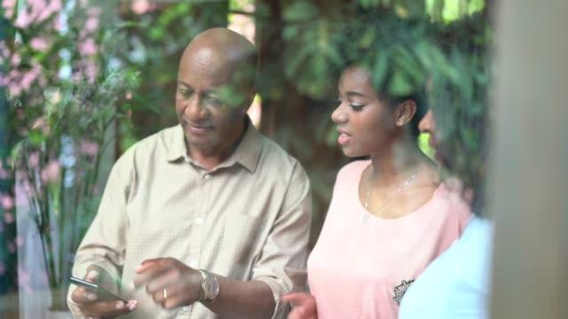 vídeos y material grabado en eventos de stock de familia africana usando el móvil mirando a través de la ventana - 50 59 años