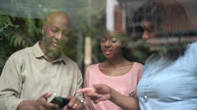 african family using mobile looking through window - 50 59 years stock videos & royalty-free footage