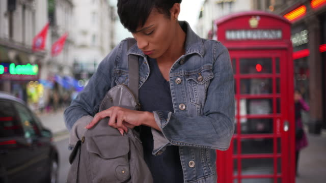 african female making sure she has everything in her purse in london street - borsetta video stock e b–roll