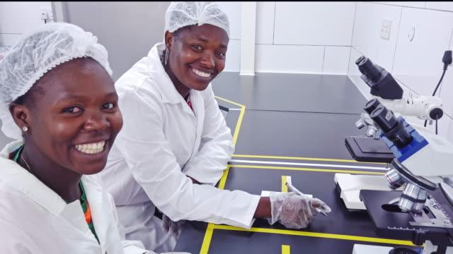 african female scientist smiling bei der kamera - haarnetz stock-videos und b-roll-filmmaterial
