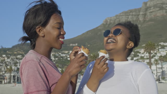 african friends eating ice cream in the beach - frozen food stock videos & royalty-free footage