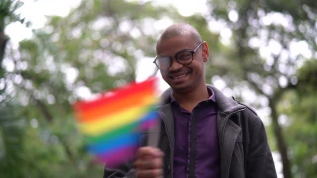 african gay man waving rainbow flag - lgbtqi people stock videos & royalty-free footage