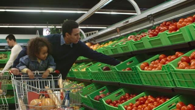 african girl helping dad with shopping in food store - 生鮮食品コーナー点の映像素材/bロール