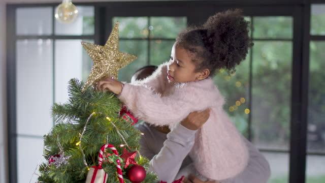 vídeos de stock, filmes e b-roll de criança africana com o pai decorando árvore de natal e colocando a estrela em cima, família feliz e conceito de cena de natal - bola de árvore de natal