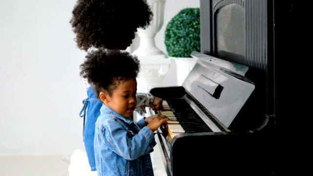 african girl playing piano - piano stock videos & royalty-free footage