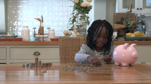 vidéos et rushes de ms african girl playing with coins and piggy bank/ cape town/ south africa - tirelire