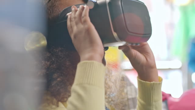 African girl playing with VR glasses