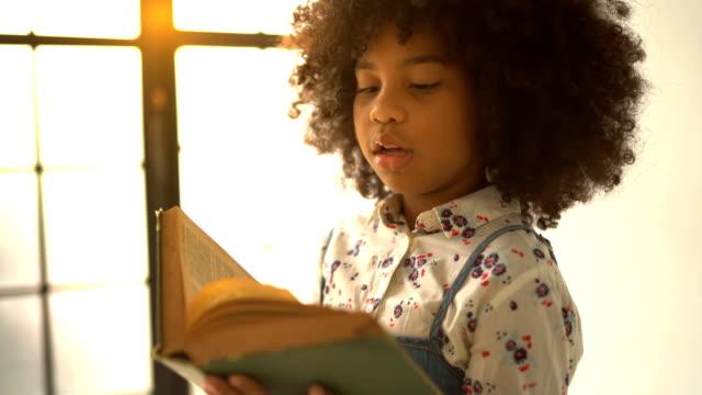 vídeos de stock, filmes e b-roll de livro de texto africano da leitura da menina - novela