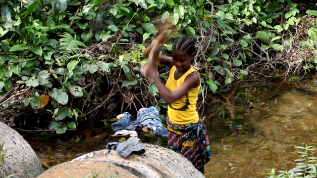african girl washing clothing in a river - teenage girls stock videos & royalty-free footage