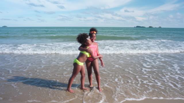 vídeos y material grabado en eventos de stock de chicas africanas conseguir por el codo de contacto en la playa - codo