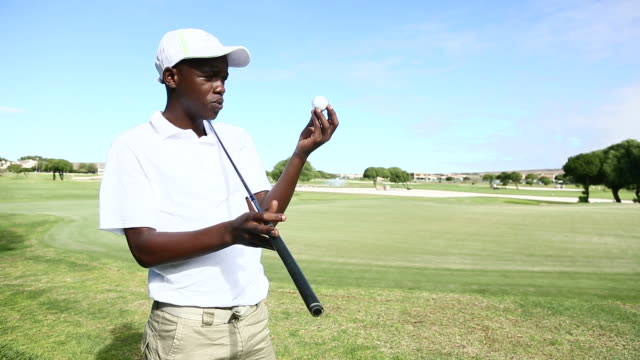 african golfer analysing the quality of his golf ball - golfer stock videos & royalty-free footage