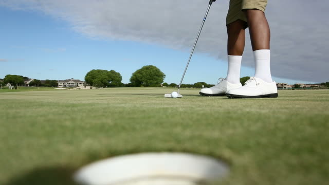 african golfer excited about hitting a ball into the hole - golf shoe stock videos & royalty-free footage