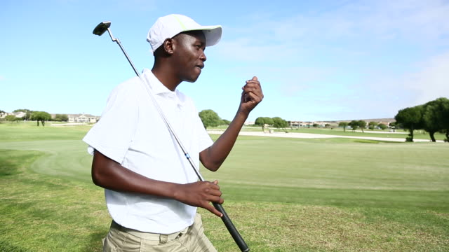 African golfer playing with his golf ball and walking away