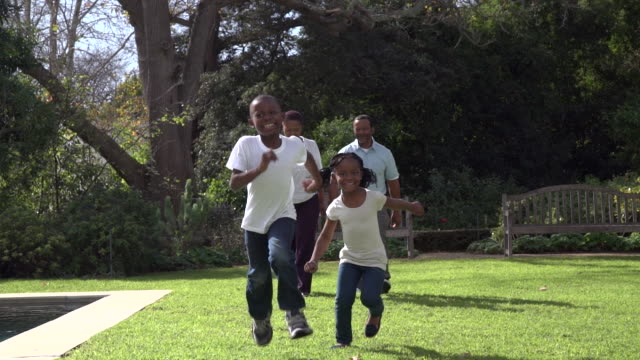 LS of African grandchildren and seniors running towards camera in garden/ Cape Town/ South Africa