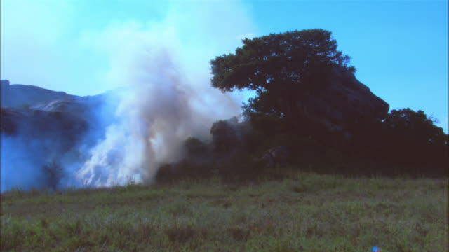 ws african grassland with rocky outcrop and smoke plume in foreground - outcrop stock videos & royalty-free footage