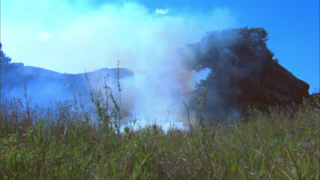 ws african grassland with rocky outcrop burnt grass and smoke in foreground - outcrop stock videos & royalty-free footage