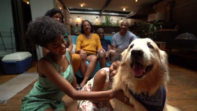 Familia hispana africana junto en casa disfrutando del perro