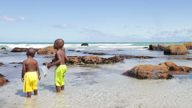 african kids playing on the beach - swimming shorts stock videos and b-roll footage