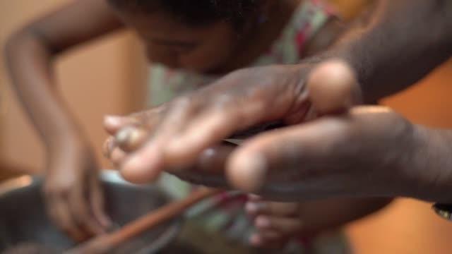 vídeos de stock e filmes b-roll de african latino grandfather teaching their grandchild how to cook at home - they are preparing brazilian brigadeiro - domestic kitchen