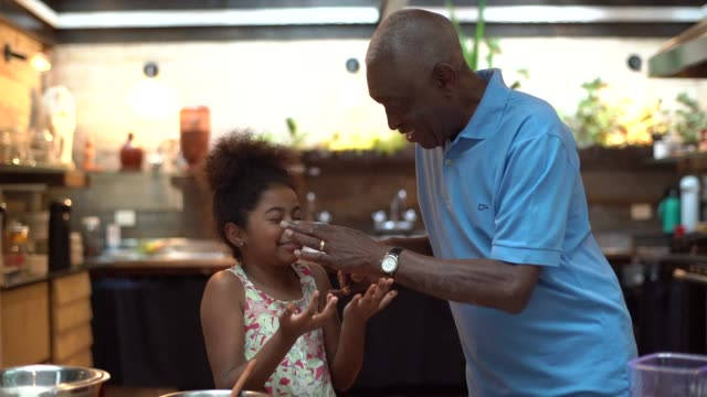 african latino grandfather teaching their grandchild how to cook at home - they are preparing brazilian brigadeiro - messy stock videos & royalty-free footage