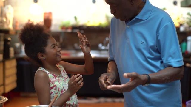 vídeos de stock, filmes e b-roll de avô de latino africano ensinando seu neto a cozinhar em casa - eles estão preparando o brigadeiro brasileiro - avô