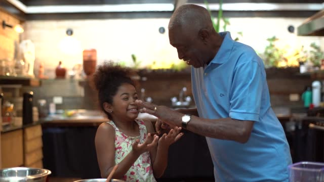 african latino grandfather teaching their grandchild how to cook at home - they are preparing brazilian brigadeiro - grandchild stock videos & royalty-free footage