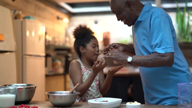 african latino grandfather teaching their grandchild how to cook at home - they are preparing brazilian brigadeiro - assistance stock videos & royalty-free footage
