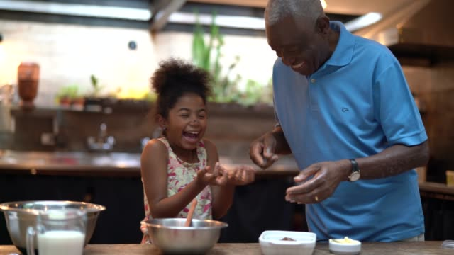 african latino grandfather teaching their grandchild how to cook at home - they are preparing brazilian brigadeiro - grandparent stock videos & royalty-free footage