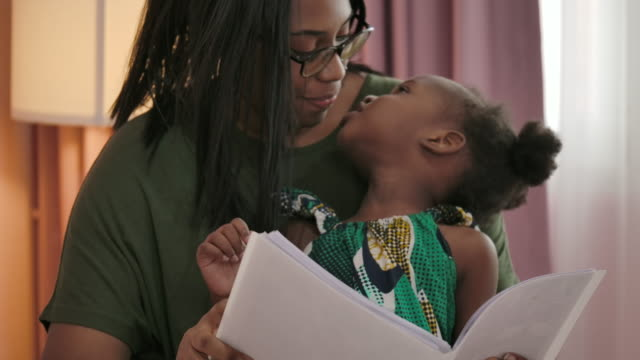 african little girl and her mother have a time together on bed at home. - one parent stock videos & royalty-free footage
