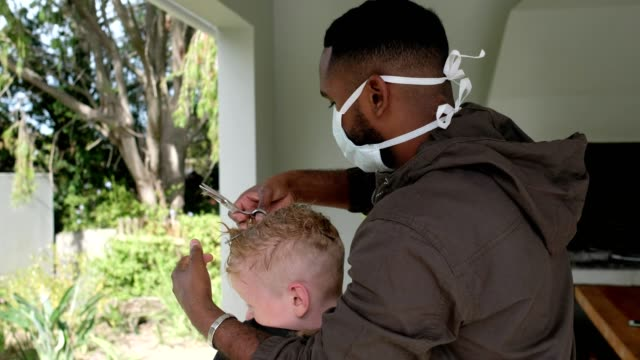 african male barber with face mask cutting a boys hair at home - barber stock videos & royalty-free footage