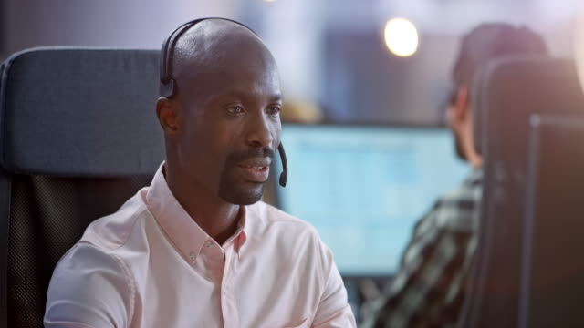 african male call center agent smiling while providing customer support - customer service representative stock videos & royalty-free footage