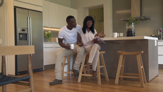 ls  african man and woman sitting in kitchen talking and drinking coffee/ woman reading magazine/ cape town/ south africa - magazine stock videos & royalty-free footage