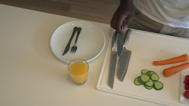 stockvideo's en b-roll-footage met ha ms african man chopping and preparing vegetables/ cape town/ south africa - tafelmanieren