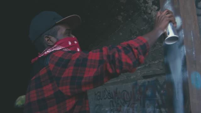 African man in bandana drawing graffiti