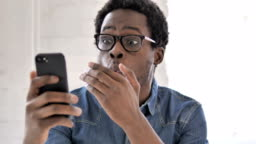 African Man in Shock while Using Smartphone