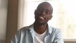 African man looking at camera talking video calling, webcam view
