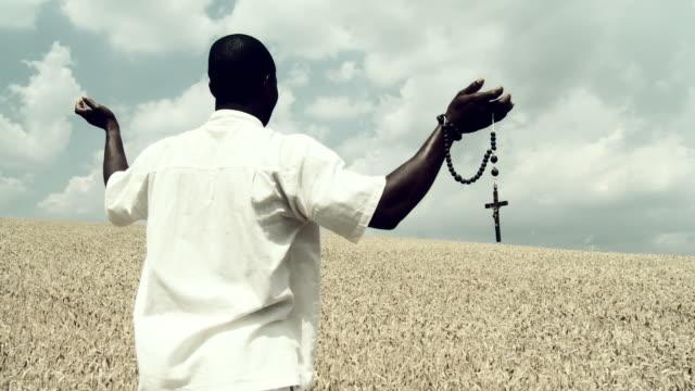 vídeos de stock, filmes e b-roll de grou hd: homem africano orar de trigo - religião