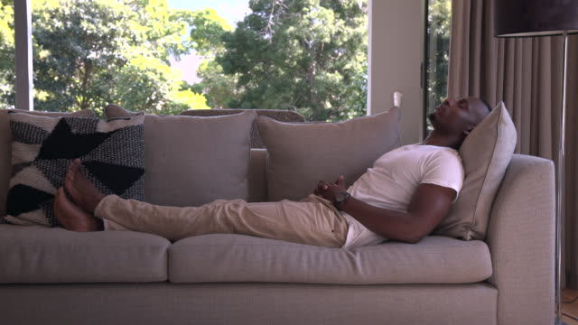 ls african man relaxing on sofa/ cape town/ south africa - relaxation stock videos & royalty-free footage