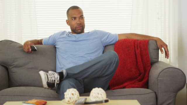 african man sitting on couch watching tv - laziness stock videos & royalty-free footage