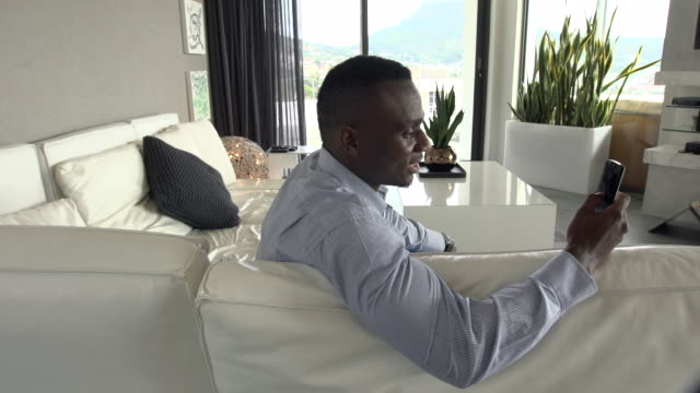 MS African man sitting on sofa using mobile phone/ Cape Town/ South Africa