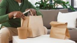 african man unpacking takeaway food at home