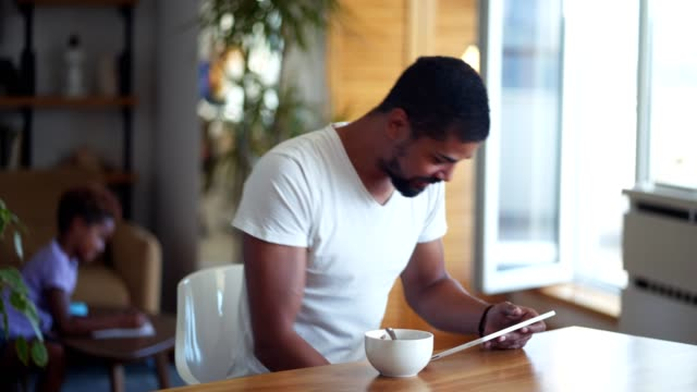 african man using tablet while having breakfast - breakfast cereal stock videos and b-roll footage