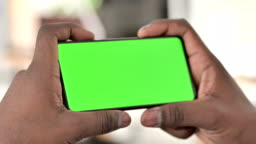 African Man Watching Video on Chroma Key Smartphone